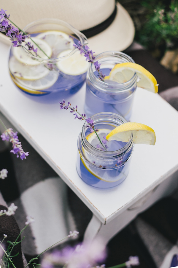 Homemade lavender lemonade with fresh lemons on a white wooden tray in a lavender field